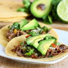 Shredded beef served on skillet warmed tortillas topped with salsa, avocados, cilantro and a squeeze of fresh lime juice.