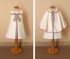 Pour une petite fille de 12 mois, une robe Suzanne en satin de coton blanc et liberty Eloïse rose doublée de voile de coton associée à une petite cape en satin de coton doublée polaire à col claudine et bordée de biais. la cape se ferme par une nouette;...                                                                                                                                                                                 Plus