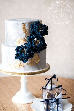 Marbled wedding cake with navy blue sugar peonies and 24k gold leaf.