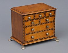 """Miniature mahogany chest of drawers with inlaid ebonized chevron pattern around drawers, brass knobs, brass hairy paw feet.  Possibly a salesman's sample.      English Circa 1850     Height: 8"""" 