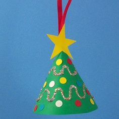 Miniature Christmas tree ornament decorated with paper punches, glitter and ribbon.