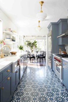 Galley style kitchen with patterned floor and blue cabinets.