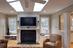 This bright family room opens directly into the kitchen at right, flanked by white carved wood pillars, with light hardwood flooring uniting the spaces. A black fireplace with white wood mantle stands flanked by a pair of recessed windows with full cabinetry and shelving beneath.