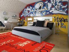 En el primer dormitorio hay una cama muy grande. En el suelo, delante de la cama, hay una alfombra naranja. A la izquierda de la cama hay una lampara. En el dormitorio hay un escritorio, una silla y una mesilla de noche con una planta encima. En la pared detras de la cama hay algunos murales.