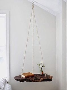 Mix things up this fall by hanging a piece of wood from the ceiling to easily create a practical nightstand.