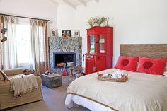 Tres casas con estilo campo  En el dormitorio principal, se proyectó una chimenea en esquina. Banquito de tapizado en barracán bordado (Carolina Hardoy). Sofá de dos cuerpos con manta tejida en el apoyabrazo. Un baúl antiguo rescatado de un galpón.