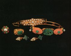 Gold , including and gold ring inlaid with a green jade ring and another inlaid with various jewels, two gold bracelets, one inlaid with pearl, and the other inlaid with green jade and red coral, and earring, Qing Dynasty, on display in the Forbidden City Palace Museum collection.
