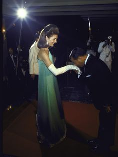 Former First Lady Jacqueline Kennedy graciously accepting kiss on hand from Cambodian Prince Norodom Sihanouk during an unofficial November diplomatic visit, Phnom Penh, Cambodia, 1967, photograph by Larry Burrows.