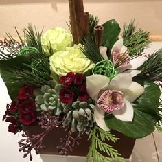 A Winter Texture Box with Super Green roses, Sweet William, miniature Cymbidium orchids, Tree Ivy, naked Eucalyptus, cedar, and fir accented with Cinnamon sticks and wire balls.