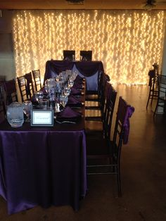 Eggplant feasting table linen and sashes, black chargers and eggplant napkins in front of sweetheart table