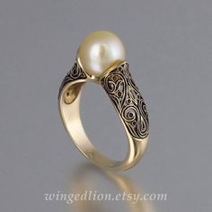 Inspired by the Renaissance art, this breathtaking ring was designed by the artist and jewelry designer Sergey Zhiboedov. The ring will be custom made in 14K gold in the size specified by the customer. The ring is adorned with intricate lace-like floral carvings, and set a genuine 8.5mm Golden Sea Pearl. The ring can be made in any size from 5 to 9.5.  The 14k yellow gold ring is shown with an antique tarnish (black rhodium plating), which adds contrast and shows off the beautiful carvings…