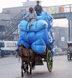 LAHORE: May04 – An over loaded horse driven cart passing through Ring Road, in Lahore.