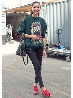 NYFW Model Street Style: Liu Wen. Graphic sweatshirts, black skinnies, and red trainers.