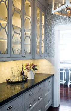 Contemporary butler's pantry features glass honeycomb cabinets lined with shelves over gray drawers adorned with polished nickel cup pulls paired with a black granite countertop and a white subway tiled backsplash.