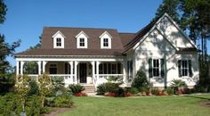 Close to how I picture my dream home:  wrap around porch, two story, white, I cant see the door but it should be red  ; ) and a big ol' yard