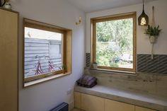 a que reveste o piso e sobe pelas paredes da cozinha, criando nichos para manter os utensílios à mão. Aço inoxidável na bancada, banco de concreto próximo à janela e ladrilhos hidráulicos com est