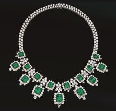 EMERALD AND DIAMOND NECKLACE.  The front decorated with a fringe of 7 emerald-cut emeralds suspended from a necklace set with 8 additional emerald-cut emeralds alternating with diamond-set foliate clusters, the total emerald weight approximately 55.00 carats, set throughout with 14 marquise-shaped and 372 round diamonds weighing a total of approximately 61.50 carats, mounted in platinum, length 15½ inches.