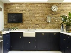 Chiswick kitchen by Neptune Kitchens with bespoke pantry unit, concrete floor, exposed brick wall, Mercury range oven, Belfast sink, Caesarstone composite worktop