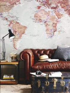 The world map, trunk, and classic tufted leather couch are perfect for my future library!