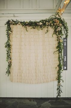 This ceremony backdrop is just a straight-up shower curtain with garland strung around the top. That greenery does wonders!