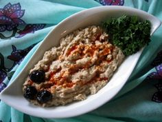 BABA GANOUSH. 1 large eggplant  2-3 clove garlic, do not peel  4 tbsp tahini (sesame seed paste)  2 tbsp yogurt, plain  3-4 tbsp lemon juice  1/2 tsp cumin  Salt    Red Pepper Sauce:  1 tsp olive oil  1/2 tsp paprika  1/2 tsp cayenne pepper