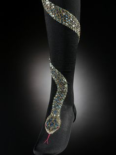 Stockings, France, 1900 - Pair of black silk knitted stockings embroidered with green sequins and green and gold beads. Decorated with a winding silver snake that curls twice around the lower leg and whose head rests on the forepart of foot.