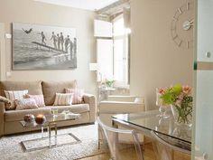 Rugs help to delimit space. Salón comedor en tonos beige y con muebles de cristal.