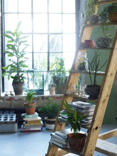 An old ladder painted white and distressed and stacked with books and plants could look cute against your red wall in the corner