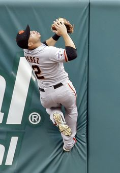 San Francisco Giants center fielder Juan Perez climbs the outfield wall to catch a ball hit by St. Louis Cardinals' Stephen Piscotty for an out during the first inning, Wednesday, Aug. 19, 2015, in St. Louis.