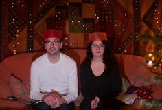 A deadpan couple wear paper hats at Christmas Time