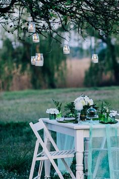 Festive table decorated with branches of greenery, stands on green grass in the area of wedding party. Town And Country, Country Living, Rustic Patio, Rustic Background, Branch Decor, Country Scenes, Lanterns Decor, Al Fresco Dining, Shabby Chic Style