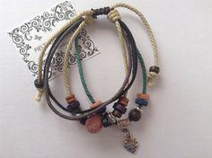 Pulsera de cuero y cordón con nudo corredizo, abalorios de colores y charm plateado corazón.