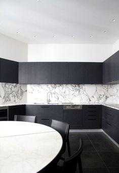 black & white kitchen, dark cabinets with grey veined marble as backsplash, black floor tile