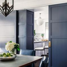 A chic dining room boasts a geometric iron pendant illuminating a gray dining table lined with blue leather dining chairs. A blue door with brass hardware opens to a magnificent kitchen. Grey Dining Tables, Leather Dining Chairs, Dining Rooms, Kitchen Designs Photos, Best Kitchen Designs, Kitchen Ideas, Door Design Interior, Interior Doors, Apartment Renovation