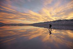 Man walks across glassy surface of salt flat - Salt Flats, Utah, United States