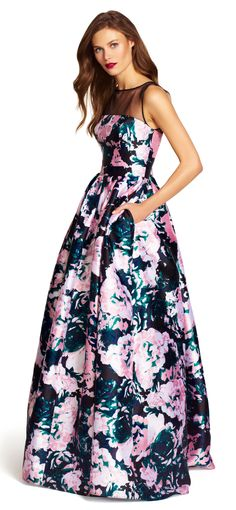 Beautiful vibrant blooms cascade across this stunning ball gown, featuring an illusion neck and pockets at both sides.