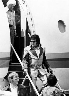 Cigar in hand, Elvis Presley walks down the ramp after arriving in Charleston, West Virginia on July 11, 1975, for the first of three concerts in the West Virginia capital city. Elaborate security precautions kept Presley a safe distance away from the crowd which greeted him at the Kanawha Airport and at his downtown hotel. More than 18,000 tickets were sold for the concerts, one Friday at night and two Saturday. (AP Photo)