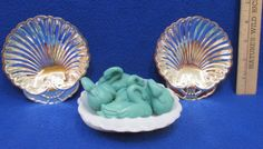 The 2 silver plated shell shaped trays are made by Old Hampshire silversmiths. The Milk Glass dish has amazing texture and detail. I have included 4 Teal Colored Molded Soaps in the shape of swans.