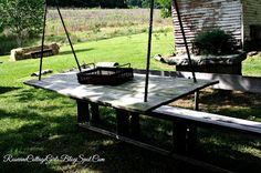 A suspended table and bench is waiting your wedding or party guests at the Fly Creek Farm at a wedding shot by Rosevine Cottage Girls