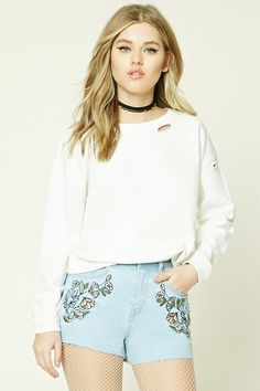 A pair of denim shorts featuring floral embroidery on the front, raw-cut hem, a five-pocket construction, and a zip fly.