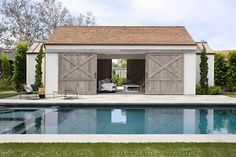 In this backyard, there a swimming pool with a pool house that has large, sliding wood barn doors that open to reveal another lounge area. #PoolHouse #SwimmingPool