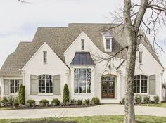 Such a welcoming home. Great buttercream color and shutters!
