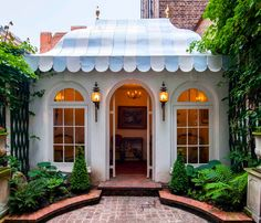 Blue and white, scalloped, tented style roof, complete with gold finials, on this garden room leading into the walled garden of a London townhouse.