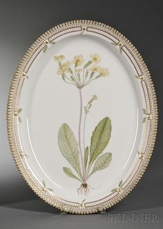 """Royal Copenhagen Porcelain """"Flora Danica"""" Pattern Serving Platter, 20th century, oval, hand-painted with a highly realistic floral specimen, crenellated gilt edge."""