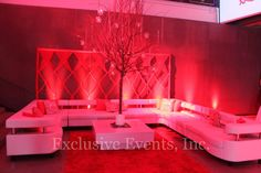 Hand braided red string curtain backdrop, bare branch tree in the center of the coffee table, filled with candles and crystals, uplit in red hue by Exclusive Events, Inc.