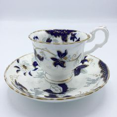 This is an antique tea cup and saucer plate with a striking cobalt blue flower design. The blue flowers and leaves are beautifully in contrast with the bright white background and are decorated with gold accents and a gold rim. The cup and the saucer plate are handpainted. This set is