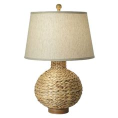Illuminate a coastal space or add a touch of natural appeal to your nightstand with this woven sea grass table lamp, showcasing a beige empire shade.