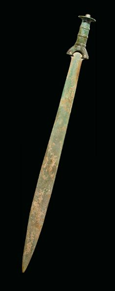 A EUROPEAN BRONZE SWORD   BRONZE AGE, CIRCA 12TH-10TH CENTURY B.C.   The long tapering blade with parallel grooves towards the tip, the hilt riveted to the blade, the arched guard with incised bands of chevrons, the ridged grip chased with three raised bands each with squares of alternating incised dashes, the disc-shaped pommel with knob terminal decorated with concentric circles including a wide band of alternating vertical dashes and concentric semi-circles