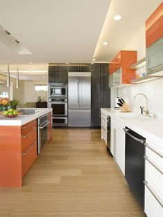 Great modern kitchen with orange, black and stainless accents.  The Bamboo floors add to the clean lines.