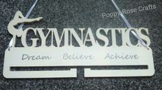 Medal holder plaque. Painted ivory with glittered letters and gymnast. Vinyl quote; Dream, Believe, Achieve. Made by me! Poppy-Rose Crafts on facebook